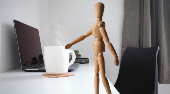Wooden figure on table with coffee cup and laptop